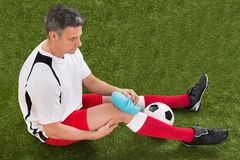 Player icing knee with ice pack. Male Soccer Player Icing Knee With Ice Pack On Field Stock Photography