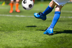 Player kicking soccer football ball. Football soccer match for children Royalty Free Stock Photography