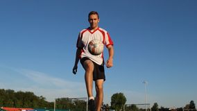 Footballer kicks the ball with his feet at soccer practice. Player kicks the ball by his feet during the session, shooting point from the bottom, white and red T stock footage