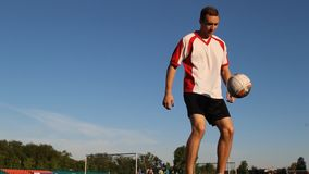 Player kicks the ball by his feet during the session, view from below. Guy kicks the ball with his feet during the training, white and red T-shirt stock video