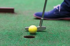 Player makes a decisive blow in the game of mini golf royalty free stock photography