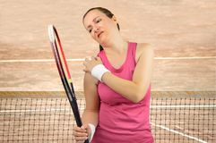 Player with pain in shoulder. Shot of a tennis player with a shoulder injured on a clay court royalty free stock photos