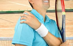 Player with pain in shoulder. Shot of a tennis player with a shoulder injury on a clay court Royalty Free Stock Photo