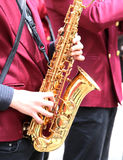 Player plays the saxophone in the brass bas outside Royalty Free Stock Images
