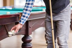 The player pulls out the billiard ball from the pocket of the table Stock Photos