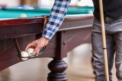The player pulls out the billiard ball from the pocket of the table Stock Photography