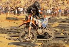 The player raises his motorcycle after falling. Enduro motorcycle competition stock photo