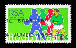Player running with Ball and Silhouettes, Rugby World Cup serie, circa 1995. MOSCOW, RUSSIA - MAY 13, 2018: A stamp printed in South Africa shows Player running stock photo