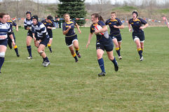 Player Running with Ball in Women's Rugby Match. Navy player running with the ball in a women's collegiate rugby match between Navy and the Brigham Young Royalty Free Stock Image