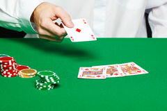 Player's hand throws a playing card Stock Photography