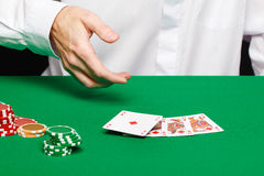 Player's hand throws a playing card Stock Photos