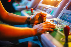 Player`s hands holding a joystick and buttons while playing on a white arcade video game. In gaming bar Royalty Free Stock Photography