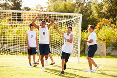 Player Scoring Goal In High School Soccer Match. With Arms In The Air Cheering Royalty Free Stock Photo