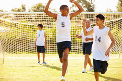 Player Scoring Goal In High School Soccer Match. With Arms In The Air Cheering Stock Images