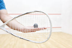 Player with squash ball and racket. Men`s hands holding squash racket and ball. Racquetball equipment. Photo with selective focus. Player prepares to serve a royalty free stock photography