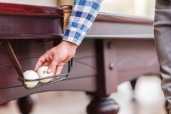 The player pulls out the billiard ball from the pocket of the table Stock Image