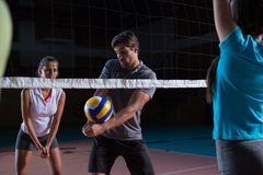 Player with teammates practicing volleyball. Male player with teammates practicing volleyball at court Royalty Free Stock Image