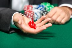Player throws dices on the green table Stock Images