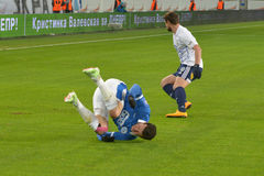 Player tumbles across the field Royalty Free Stock Photo