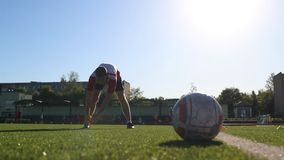 Footballer flexing his muscles during the session. Player warming up at soccer practice stock footage