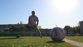 Player warming up at soccer practice. Footballer flexing his muscles during the session stock video footage