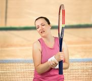 Player with wrist injury. Shot of a tennis player with a wrist injury on a clay court stock image