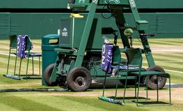 Players` chairs with towel folded over the back, and a green and purple umbrella on the grass. royalty free stock photo