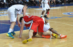Players on the floor fighting for the ball Stock Photo