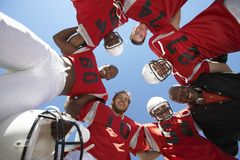 Players Forming A Huddle. Low angle view of rugby players with coach forming huddle against clear sky Stock Photo