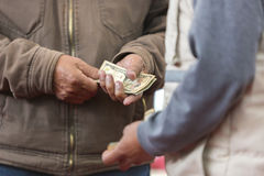 Players hands exchanging dollar money after fight in Ecuado. Hand receiving money from cockfight loser owner in Otavalo, Ecuador. Defocussed foreground stock images