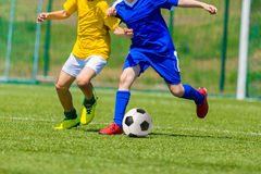 Players play football soccer game. Young boys playing football soccer game. Running players in blue and yellow uniforms Royalty Free Stock Image