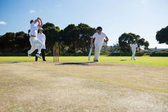 Players playing cricket match at field. On sunny day stock image