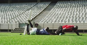 Players playing rugby match in stadium 4k. Side view of African American rugby players playing rugby match in stadium. They are tackling each other 4k stock footage
