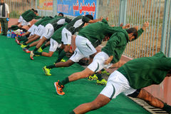 Players Stretching Before Game. SIALKOT, PAKISTAN - DECEMBER 2014: All Pakistan Annual Field Hockey Tournament Between PIA and PAF Teams at Sialkot International stock image