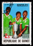 Players with trophy, 3rd winning of the African Football Cup by Hafia Football Club serie, circa 1979. MOSCOW, RUSSIA - AUGUST 18, 2018: A stamp printed in stock image