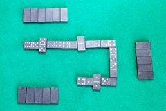 Playfield of dominoes board game with black tiles. Top view of playfield of dominoes board game with black tiles on green baize table royalty free stock photo