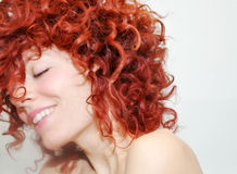 Playful. A playful young woman with vibrant red curls Royalty Free Stock Photo