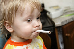Playful. The boy has stolen a cigarette at home Stock Photography