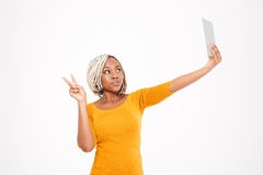 Playful african american woman making selfie and showing victory sign Stock Photography