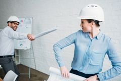 playful architects fighting with rolled building plans royalty free stock photo