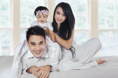 Playful asian family in the bedroom. Attractive asian family playing together in the bedroom, smiling at camera Royalty Free Stock Photography