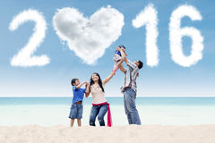 Playful asian family celebrate new year of 2016. Joyful hispanic family playing on the coast while celebrate new year with cloud shaped numbers 2016 Royalty Free Stock Photography