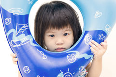 Playful asian girl with swimming float. Asian girl in swimming outfit framing his portrait with a float royalty free stock images