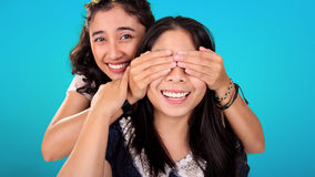 Playful Asian girls. Two smiling Asian female friends play guess who game. One girl covering her friend's eyes from behind, over blue background Royalty Free Stock Image