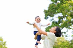 Playful Asian mother throwing up happy baby boy in the nature garden. Mother lifting up son at park stock images