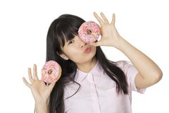 Asian woman having some fun with delicious strawberry frosted donuts. Playful Asian woman having some fun with delicious strawberry frosted donuts Stock Photo