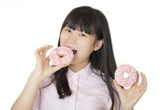 Asian woman having some fun with delicious strawberry frosted do. Playful Asian woman having some fun with delicious strawberry frosted donuts isolated on a Royalty Free Stock Images