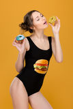 Playful attractive woman in black designer swimsuit posing with donuts Royalty Free Stock Photos