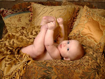 Playful Baby. Baby playing with toes, lying on golden tapestry with pillows Royalty Free Stock Photo
