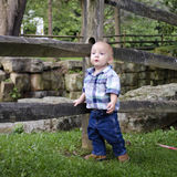 Playful Baby Boy. Baby boy posing by a wooden fence Royalty Free Stock Photos